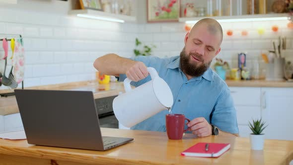 Senior Bearded Man Pours Tea or Coffee Into a Mug While Working or Studying Remotely at Home