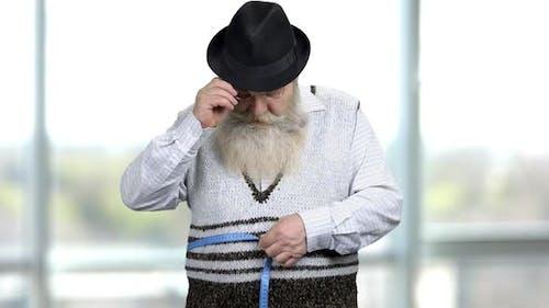 Elderly Man Measuring Hos Waist with a Blue Waistline