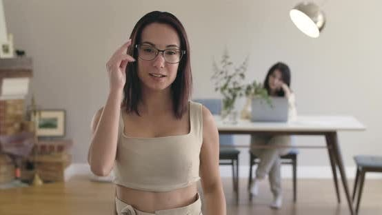 Thumbnail for Smiling Caucasian Girl Taking Off Eyeglasses and Looking at Camera. Her Friend or Sister Sitting