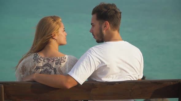 Cover Image for Man and Woman Talk Sitting at the Bench, Sea Is in the Background
