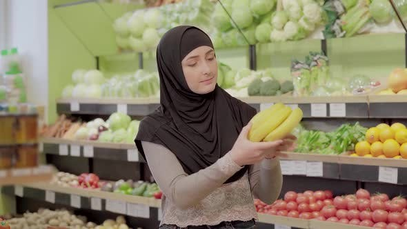 Thumbnail for Young Muslim Woman Examining Bunch of Bananas in Grocery. Portrait of Beautiful Lady Choosing Fresh