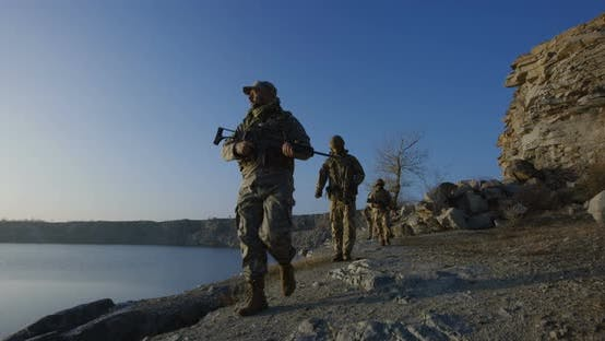 Cover Image for Armed Soldiers Walking By a Lake