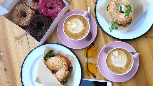 Draufsicht auf Essen auf Holztisch zum Frühstück. Kaffee, Donuts und Bagels.