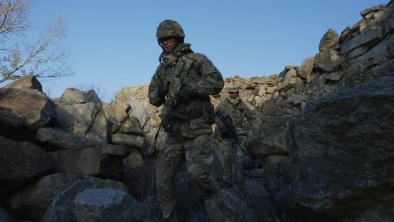 Thumbnail for Armed Soldiers Walking Over Large Rocks