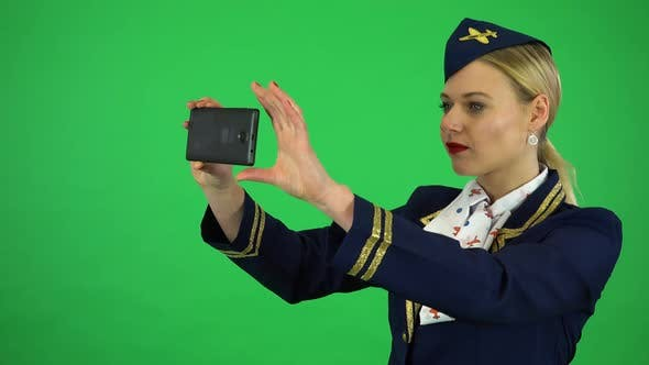 Thumbnail for A Young Beautiful Stewardess Takes Pictures with a Smartphone - Green Screen Studio