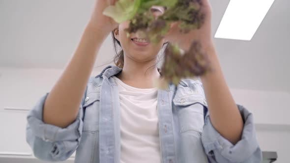 Young Asian woman making salad healthy food use organic vegetables lots.