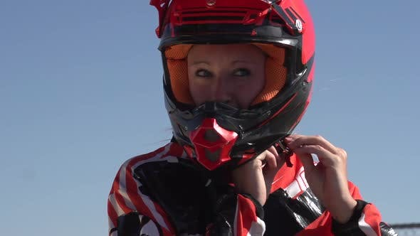 Thumbnail for A young woman bmx rider putting on helmet.