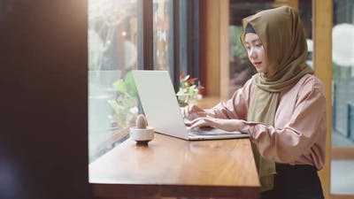 Young Asian Muslim Woman Worling in the Coffeeshop