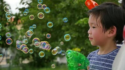 Cute Asian Child Shooting Bubbles From Bubble Gun