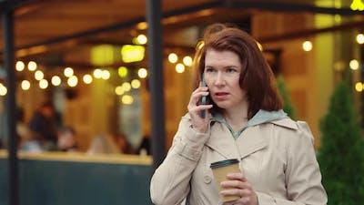 Business Woman Talking on Phone During Coffee Break