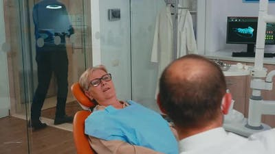 Woman with New Dental Implants Looking in the Mirror
