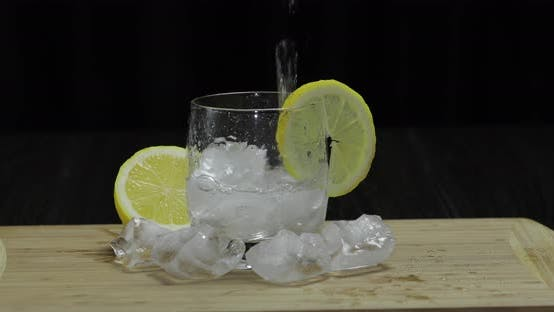 Thumbnail for Pours Lemon Juice Into Glass with Ice, Thyme and Lemon Slices