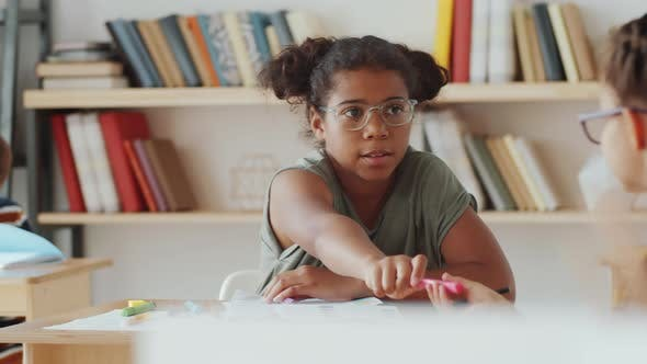 Diverse Schoolgirls Sharing Felt Tip Pens during Lesson