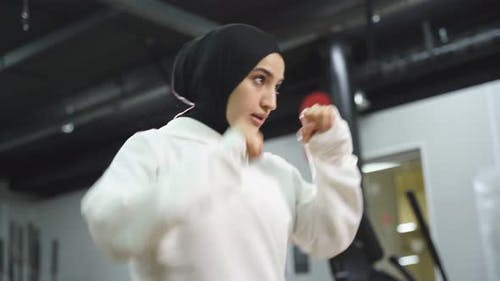 Muslim Female Boxer in a Sports Hijab is Engaged in Boxing an Arab Woman is Doing Exercises