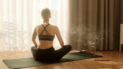 Woman doing yoga and meditating, practicing yoga at home in the morning