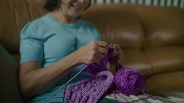 Woman Knits Scarf with Spokes Listens to Music with Headphones and Dances