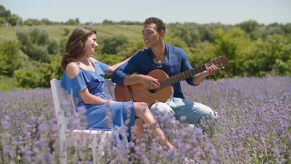 Thumbnail for Romantic Man Serenading Woman with Guitar Outdoors