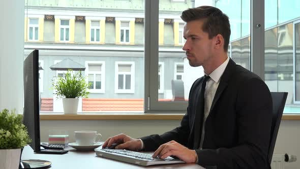Thumbnail for An office worker in a suit works serious on a computer