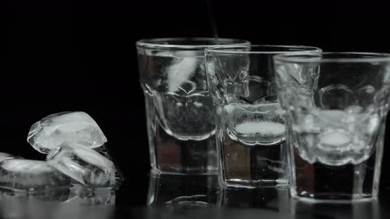 Thumbnail for Pouring Up Three Shots of Vodka From a Bottle Into Glass. Black Background
