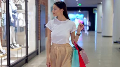 Woman Carrying Shopping Bags While Walking in Mall