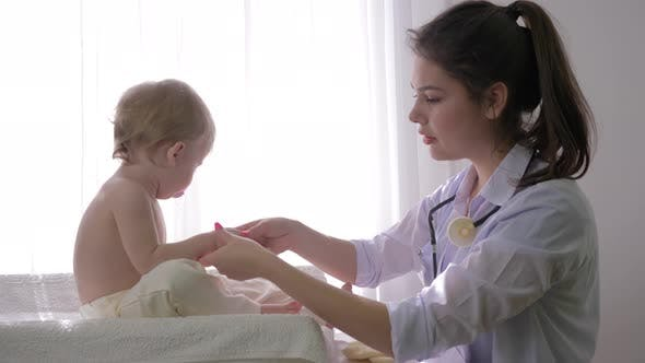 Thumbnail for Little Child at Doctor on Medical Checkup, Professional Pediatrician Woman Examines Sweet Baby Boy