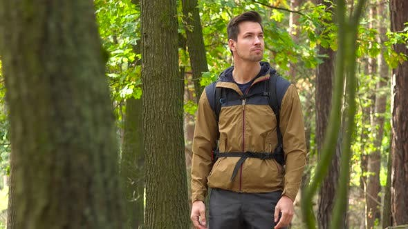 Thumbnail for A Young Handsome Backpacker Stands in a Forest and Looks Around