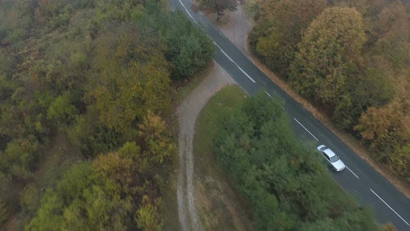 Drone Chasing White Car Driving on Misty Asphalt Road in the Mountains