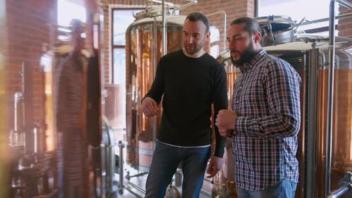Two Male Brewery Workers Talking Admiring New Shiny Equipment