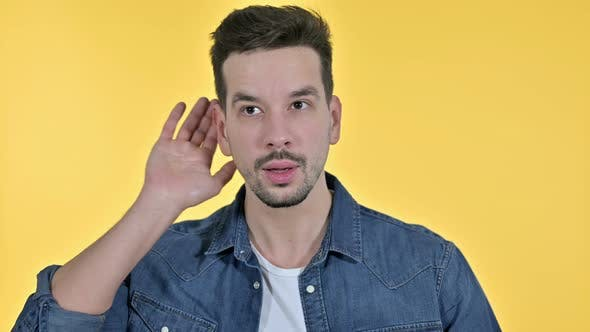 Thumbnail for Portrait of Curious Young Man Listening Secret, Yellow Background