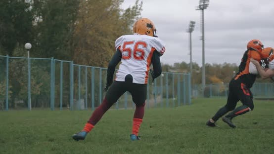 American Football, Football Players in the Game, the Player Catches the Ball and Falls To the Ground