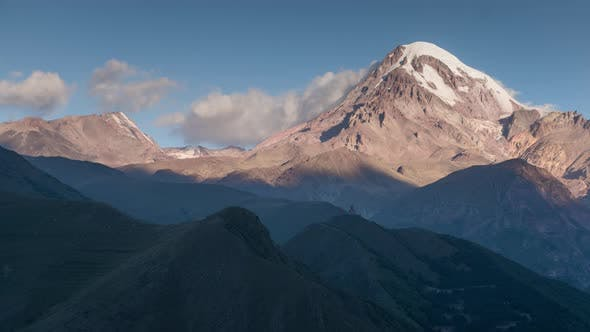 Thumbnail for Sunrise in Highlands. Kazbek Mountain Peak with Snow Cap and Glacier in Sun Rays Moving Shadows