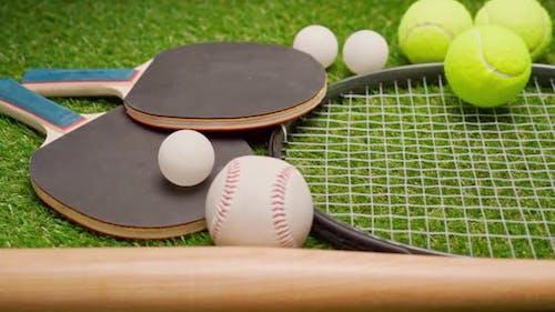 Sportgeräte-Schläger und Bälle auf Grashintergrund