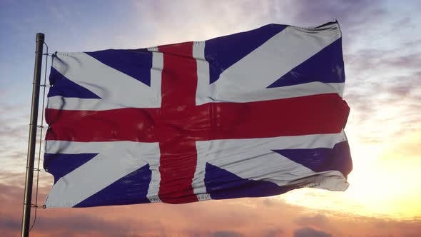 Flag of United Kingdom Waving in the Wind Against Deep Beautiful Sky at Sunset