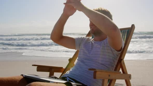 Thumbnail for Man with hands behind head relaxing on sun lounger at beach 4k