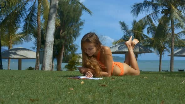 Cover Image for Blond Girl in Swimsuit Lies with Book on Green Lawn