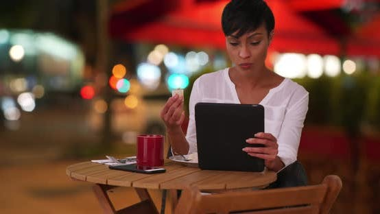 Thumbnail for African female eating outside at restaurant while watching something on tablet