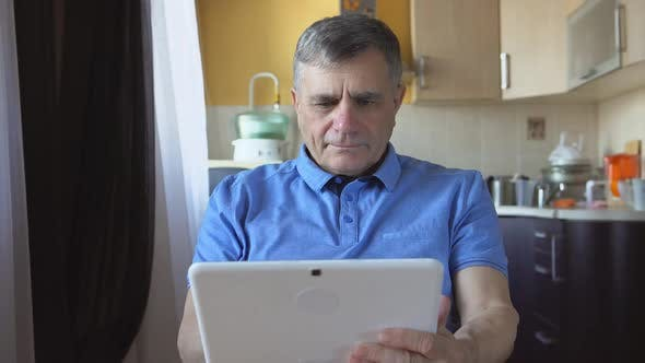 Thumbnail for Potrait Of An Aged Male At The Blue Shirt Sits And Uses A White Tablet Pc At Home