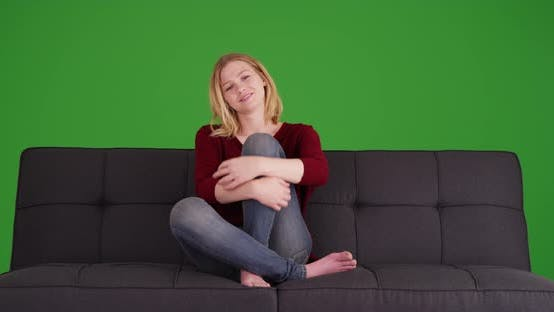 Thumbnail for Authentic twenties blonde woman sitting on couch on green screen
