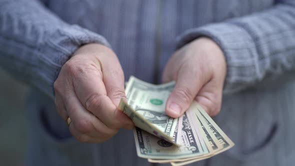 Elderly Woman Holds and Counts Cash in Arms