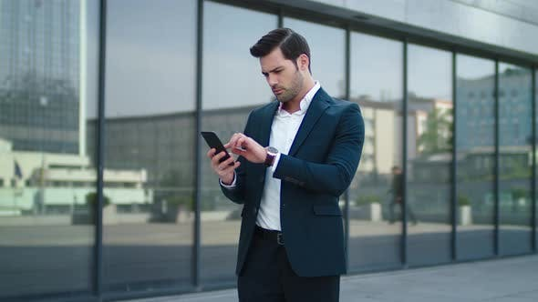 Cover Image for Closeup Man Taking Phone Out of Pocket. Businessman Celebrating Victory Outdoor