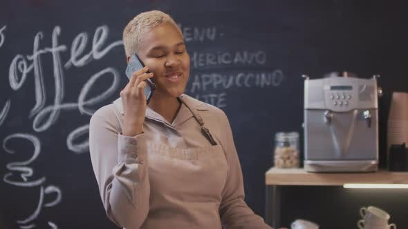 Thumbnail for Coffee Seller Talking On Phone Smiling