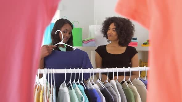 Thumbnail for African American friends shopping and trying on clothes