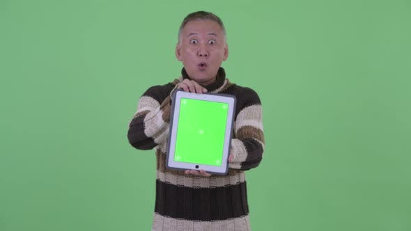 Thumbnail for Happy Mature Japanese Man Showing Digital Tablet and Looking Surprised