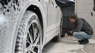 Car Service The Worker Washes Car Rims with a Soft Brush with Shampoo