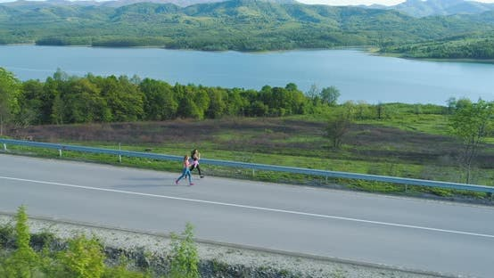 Top View of Fitness Friends Running on Country Road Near Lake