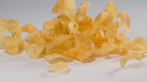 Potato Chips falling onto a white surface in slow motion