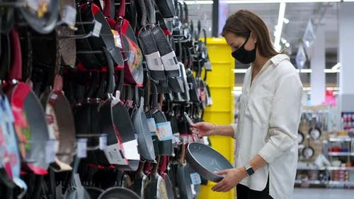 Woman Doing the Shopping in the Department of Kitchenware
