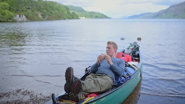 A Young Man Eating While Resting In A Boat On The River Of Caledonian Canal, Scotland - Close Up Sho