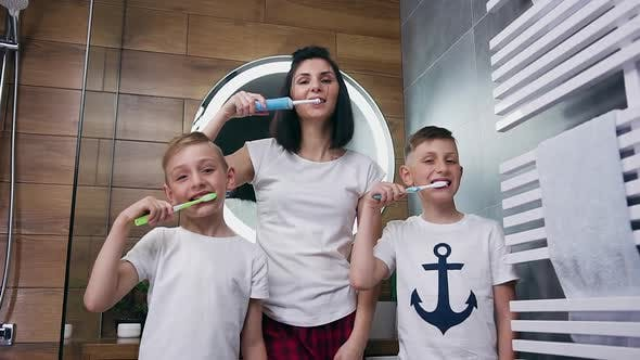 Thumbnail for Mother and Her Two Sons which Cleaning Their Teeth with Toothbrushes in the Bathroom