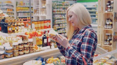 Young Woman Chooses Cheese in the Big Store
